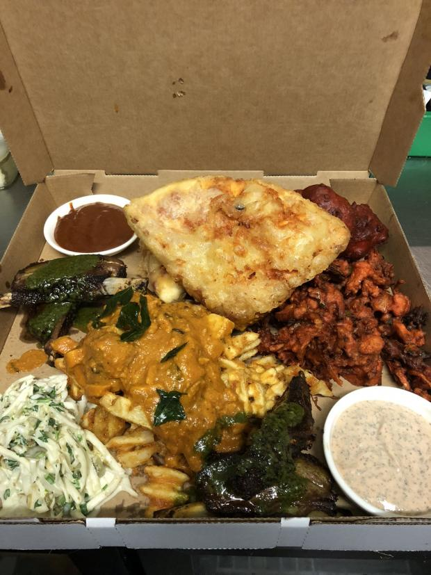 Glasgow Times: The 'Govanhill Munchie Box Part Two' contains deep fried pizza crunch, veggie pakora, chips and curry sauce, chicken tikka, two chip shop style sausages, two seekh kebabs, eight hot wings, cheddar coleslaw, and comes with homemade pink sauce and brown sauce