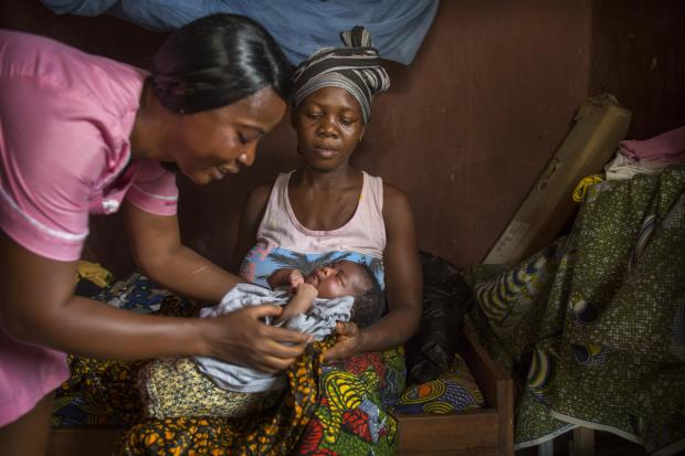 Glasgow Times: Nurse Veronica Konneh attends to Sombo Climbe who has as just given birth to a daughter, Mariama Climbe in the labour room at the village of Nyamdehun Bessima , Pujahun district of Sierra Leone. 27/2/19. Photo Tom Pilston/Christian Aid..