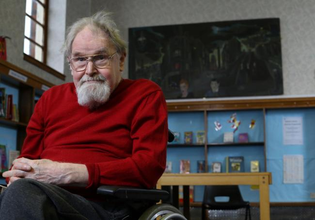 The artist Alasdair Gray pictured in Riddrie library, Glasgow below his painting 'Cowcaddens Streetscape in the Fifties' that will be on display at the library until January 2018. ..   Photograph by Colin Mearns.24 January 2017.