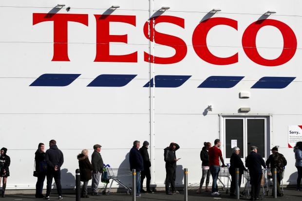 Glasgow Times: People queue outside a Tesco Extra store in Madeley, Shropshire