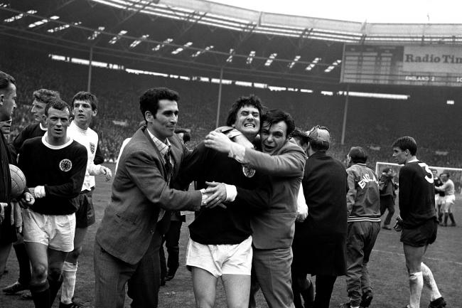 Jim Baxter is hugged by Scotland fans after an inspirational display