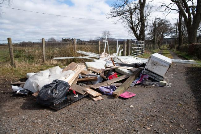 Rubbish left illegally by what is known as fly-tippers blights a country road  near a village close to Glasgow
