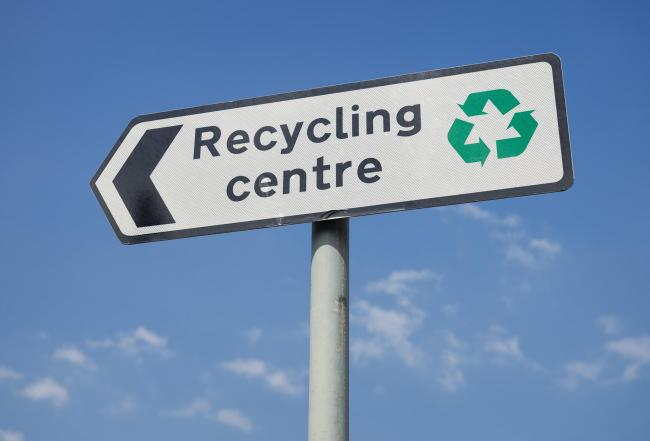 A sign for a public recycling centre, with a green recycling symbol..