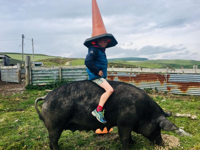 Charlie Jones, 9, sitting on pet pig Chloe to recreate Duke of Wellington statue for a school project. See SWNS story SWSCstatue. A little boy recreated the statue of the Duke of Wellington for a lockdown school project - by sitting on his pet PIG with a