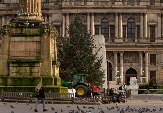 A woman walks past the Christmas tree in George Square, Glasgow. The Scottish Government is due to make an announcement tomorrow, Tuesday about a near-lockdown for west central Scotland