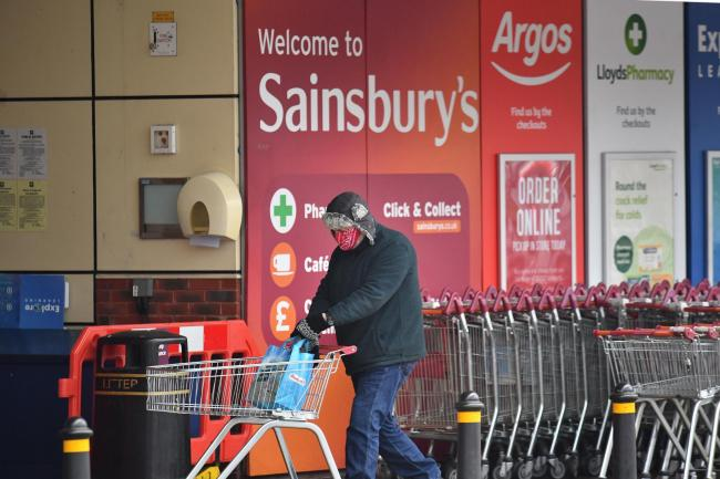 A shopper wearing a face mask enters a Sainsbury's store in south east London. Supermarkets are being called on to revert to more stringent in-store coronavirus measures with members of the public urged to respect regulations when out grocery shopping