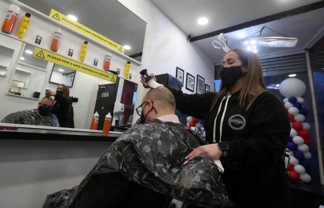 Barber Maggie McGillivray trims Sam Rosenblom's hair at Tony Mann's Barber Shop in Giffnock near Glasgow as barbers reopen across Scotland. Picture date: Monday April 5, 2021. PA Photo. See PA story SCOTLAND Coronavirus. Photo credit should read: