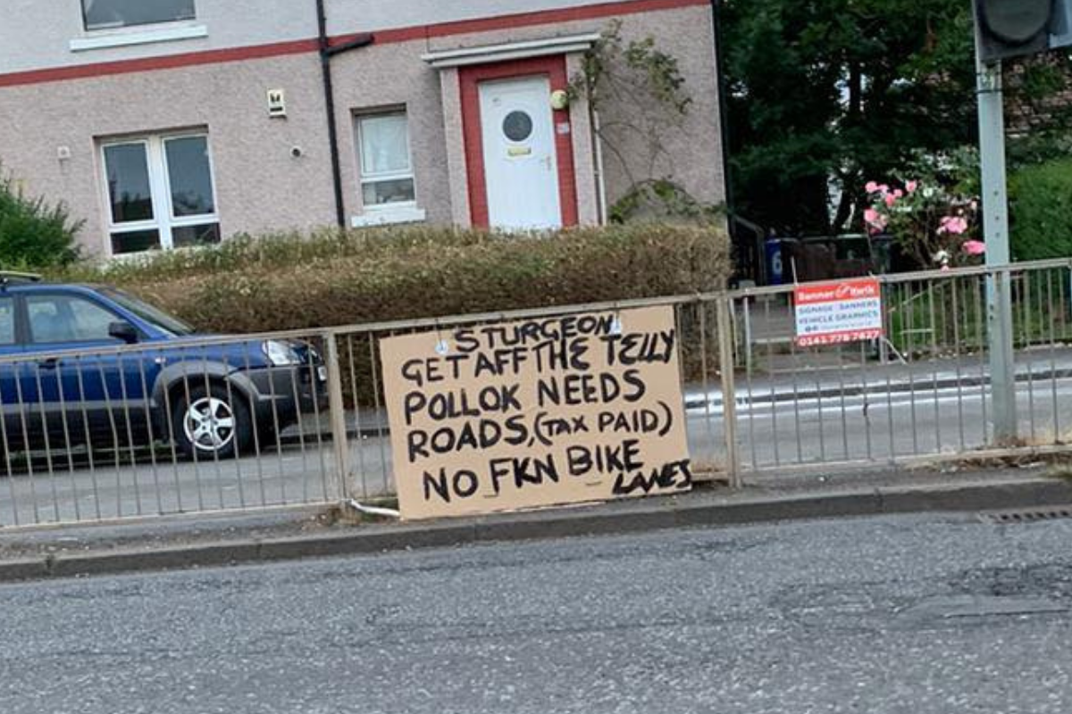 Sign reading 'Pollok needs roads, no bike lanes' appears in Glasgow's South Side