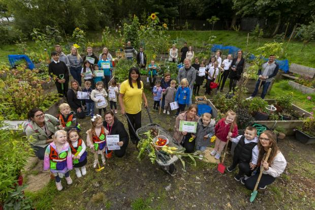 Glasgow Times: Streets forward feature on Lockheed community allotment at Glasgow's Easter House.  Photo by Susan Wilson, centered with the children of local schools, nurseries and volunteers along the Whale Barrow.