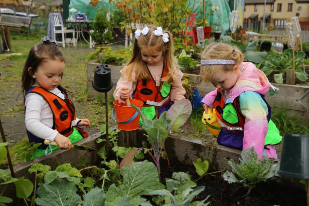 Glasgow Times: Streets forward feature on Lockheed community allotment at Glasgow's Easter House.  Pictured are St. Clair Day nursery children caring for their raised bed.  From left - Ava, Zoe and Aria..Photograph by Colin Mearns.13 September 2021. For GT, see the story