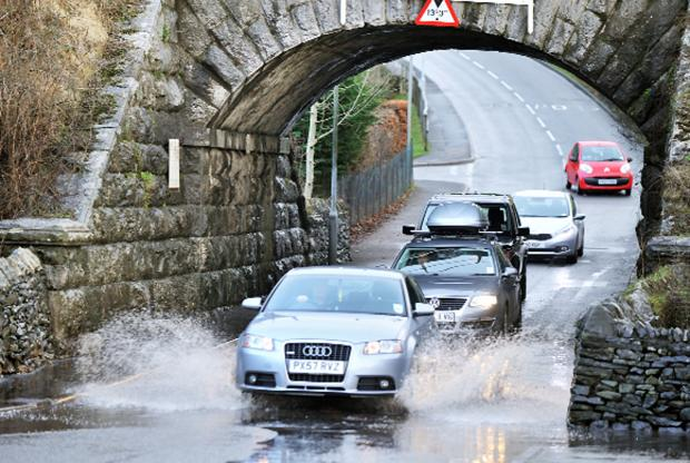 Glasgow Times: Drivers negotiate the flooding at Parkside Road