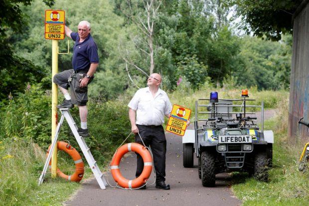 George Parsonage and volunteer Colin Munn install another sat-nav linked lifebelt by the Clyde