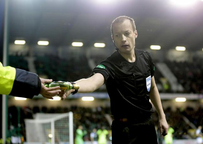 Willie Collum removes a glass bottle that was thrown at Scott Sinclair