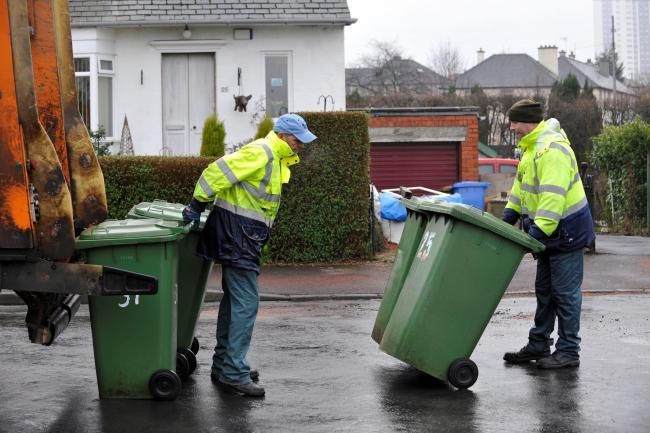 Glasgow City Council refuse collection now operating at the weekend.Refuse collectors  empty wheelie bins in Knightswood area
